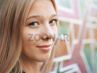 teenage girl leaning against graffiti wall