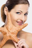 Beautiful woman holding a starfish