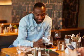 Afrikanischer Mann schreibt eine SMS im Restaurant