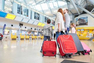Familie und Kinder im Flughafen warten auf Abflug