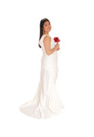 Lovely bride standing in a white gown with red rose