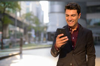 Happy Hispanic businessman using phone outside the office building