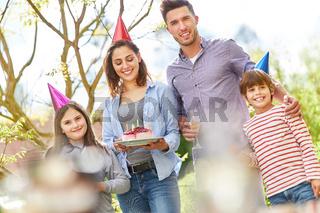 Familie mit Kindern feiern Geburtstag mit Kuchen
