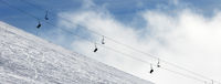 Snow off-piste ski slope and chair-lift in fog