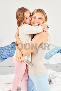 Tochter umarmt Mutter und gibt ihr einen Kuss