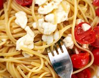 Top view of a plate of spaghetti seasoned with cherry tomatoes and fresh mozzarella with a fork ready to roll them.
