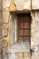 Wooden grunge closed window with wrought iron grid in stone bricks wall
