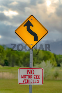 Close up view of a Winding Road Ahead sign and No Motorized Vehicles sign