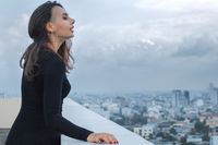 Portrait of young beautiful woman posing on rooftop with space for text
