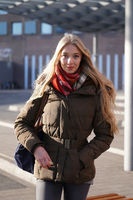 street style fashion portrait of young woman waiting at bus station