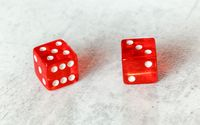 Two translucent red craps dices on white board showing Easy Eight number 5 and 3