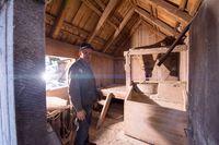 portrait of a miller in retro wooden watermill