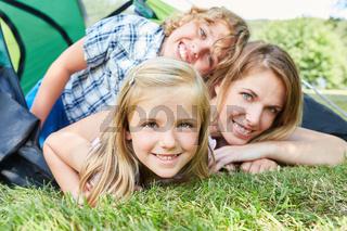 Kinder zusammen mit Mutter vor dem Zelt