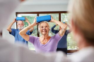 Senioren machen eine Übung mit dem Yogablock