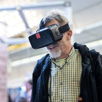 Senior man wearing virtual reality goggles watching virtual reality presentation.