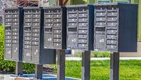 Panorama Row of cluster mailboxes with numbered compartments on a sunlit sidewalk