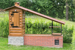 Small homemade smokehouse with stone base and long inlet flue