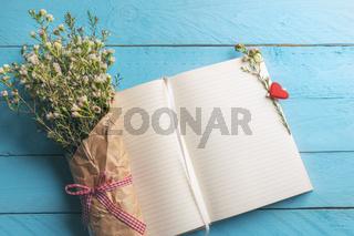 Flower bouquet on an empty open notebook on a blue table