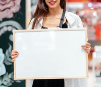 Smiling brunette woman holding white blank board