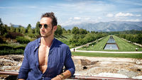 Handsome muscular man posing in European luxury garden