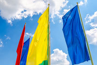 Colorful flags in the wind against the blue sky