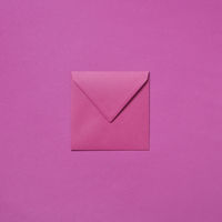 Craft envelope mock-up for invitation on a magenta background.