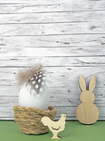 Easter background with Easter egg, Easter bunny  and cock isolated on green in front of wood
