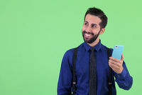 Young happy bearded Persian businessman thinking while using phone