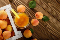 Apricot smoothie in mason jar and crate on wooden table. Top view