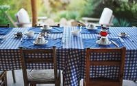 Table with empty plates and coffee cups, blue chequered tablecloth, ready for morning breakfast, blurred green foliage in background - eating at tropical holiday resort