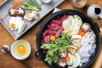 Traditional Sukiyaki pot with Kobe Beef and Vegetable as close-up on wooden table