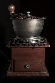 Walnut coffee grinder full of coffee beans on black background