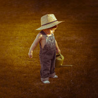 Autumn, little gardener in a garden of a house with a small green watering can watering the plants, wearing a cowboy breastplate and a straw hat