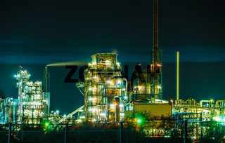 Chemiefabrik, Raffinerie mit vielen Lichtern entlang der Rohre und Gebäude