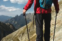 The body of man with a backpack and trekking poles stands on top of a rock against the background rocky valley high in the mountains. The concept of tourism and easy trekking in the mountains outdoor