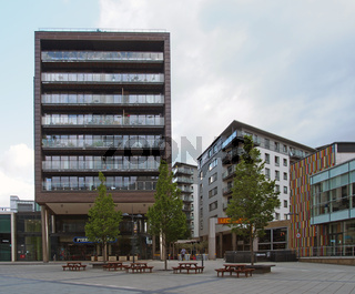 bars restaurants and modern apartment buildings in the leeds dock area around a public square with trees and benches