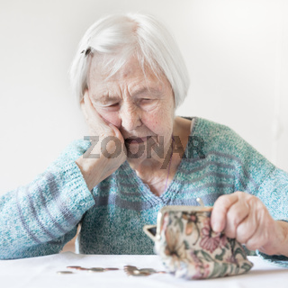 Concerned elderly woman sitting at the table counting money in her wallet.