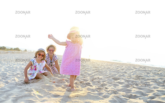 Happy baby girl and her sisters playing in sand on a beautiful beach
