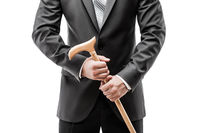Businessman in black suit holding walking cane stick