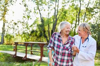 Ärztin hilft einer Seniorin beim Lauftraining