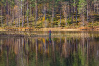 Man fly fishing in the woods lake