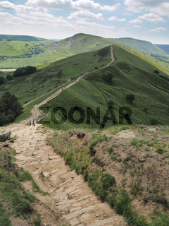 The steep rocky descent of Back Tor with Mam Tor in the background, Peak District National Park, UK