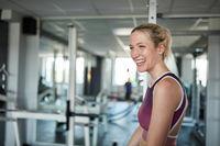 Lachende junge Frau im Fitnesscenter