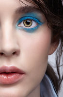 Closeup macro portrait of female face. Human woman half-face with unusual beauty makeup. Girl with perfect skin, green pistachio colour eyes and blue shadows make-up