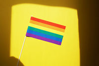 rainbow flag gay or lgbt pride symbol against yellow background with shadow frame