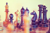 Old wooden chessmen on the chess board