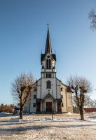 Bamble Church, large wooden church buildt in 1845. Winter, snow, blue sky. Front view. Vertical image.
