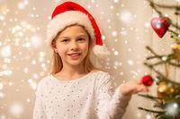 happy girl in santa hat decorating christmas tree