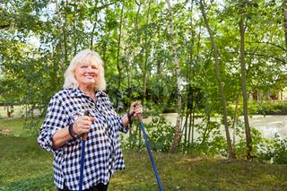 Senior Frau mit Übergewicht beim Nordic Walking