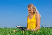 Young blond dutch woman reads book in grass